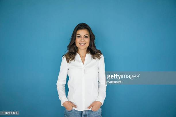 portrait of smiling woman standing in front of blue wall - all shirts stock pictures, royalty-free photos & images