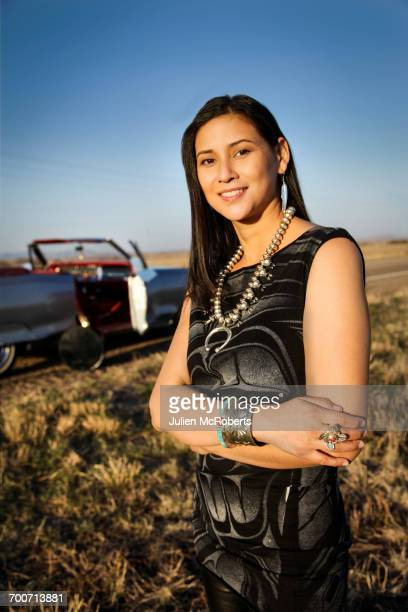 Portrait of smiling woman standing in grass near car