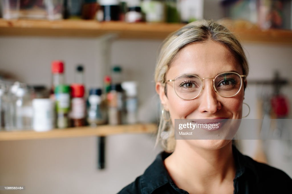 Portrait of smiling woman standing in kitchen at home : Stockfoto