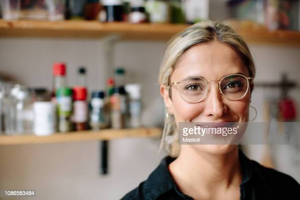portrait of smiling woman standing in kitchen at home - women stock-fotos und bilder