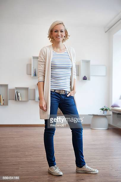 portrait of smiling woman standing in modern living room - one mid adult woman only stock pictures, royalty-free photos & images