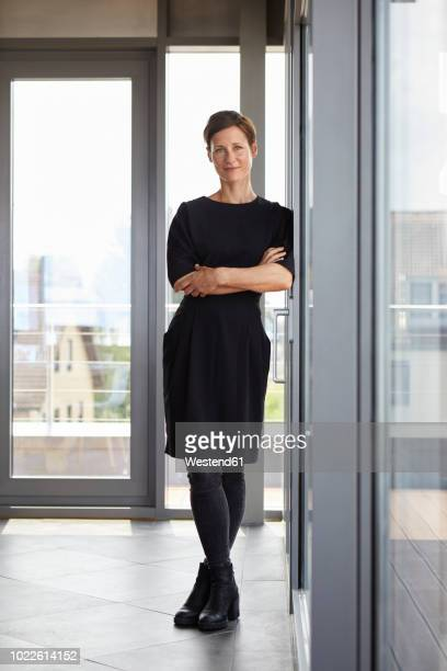 portrait of smiling woman standing in office - mid adult women stock pictures, royalty-free photos & images
