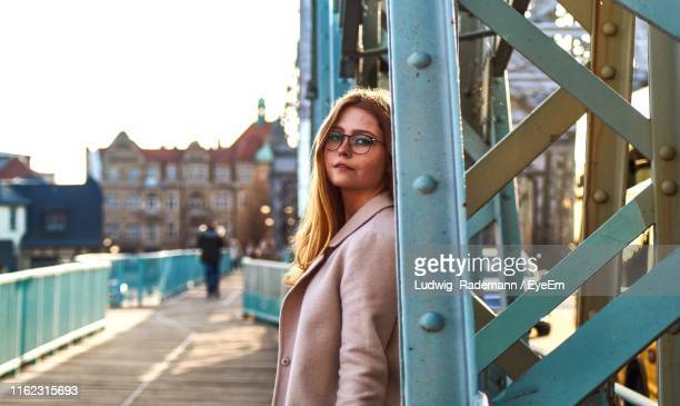 portrait of smiling woman standing on bridge - rademann stock pictures, royalty-free photos & images