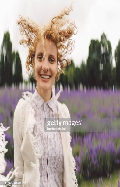 portrait of smiling woman standing on field - bortes cristian stock-fotos und bilder