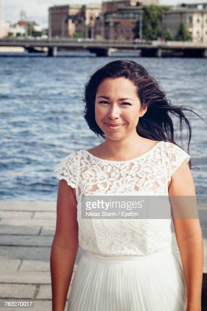 portrait of smiling woman standing on footpath against river in city - niklas storm eyeem stock photos and pictures