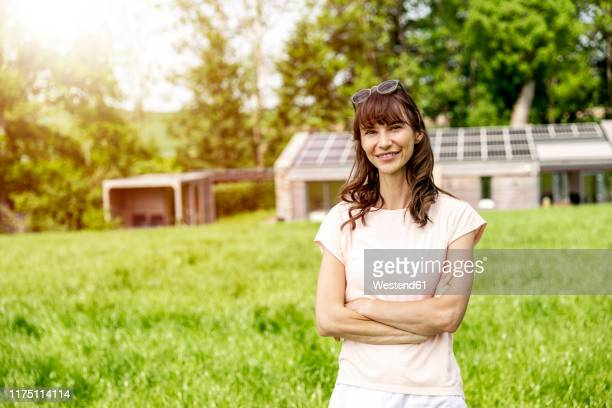 portrait of smiling woman standing on meadow in front of a house - solar equipment stock pictures, royalty-free photos & images