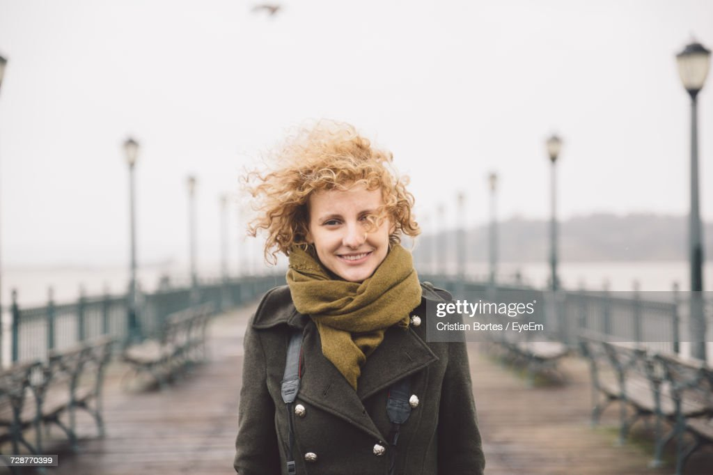 Portrait Of Smiling Woman Standing On Pier By Sea Against Clear Sky : Stock Photo