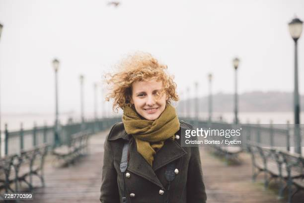 Portrait Of Smiling Woman Standing On Pier By Sea Against Clear Sky