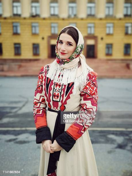 portrait of smiling woman standing on road against building - traditional clothing stock pictures, royalty-free photos & images