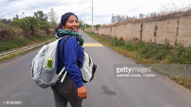 portrait of smiling woman standing on road - three quarter length stock pictures, royalty-free photos & images