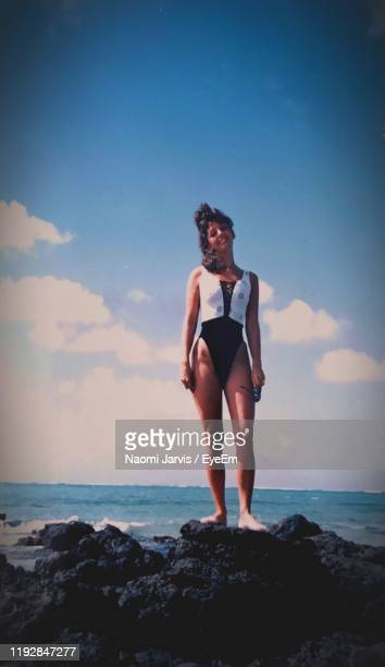 portrait of smiling woman standing on rock by sea against sky - naomi jarvis stock pictures, royalty-free photos & images
