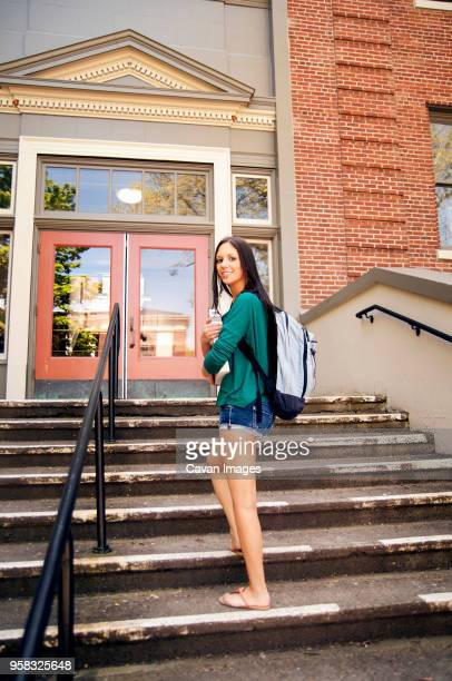 Portrait of smiling woman standing on steps against building