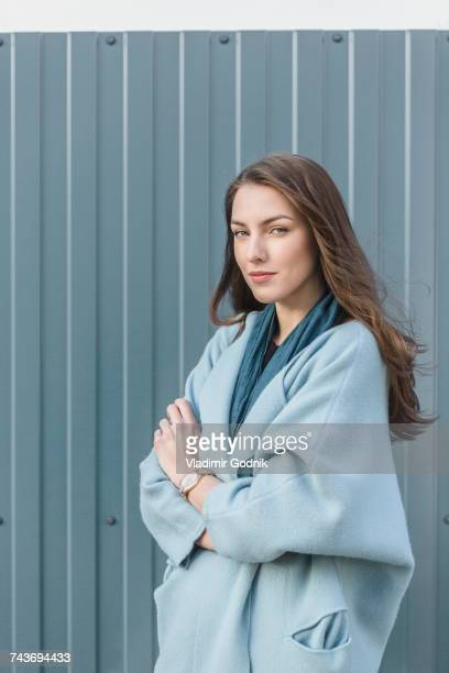 portrait of smiling woman standing with arms crossed against gray wall - long coat stock pictures, royalty-free photos & images