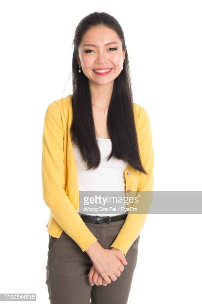portrait of smiling woman standing with arms crossed against white background - black hair stock pictures, royalty-free photos & images