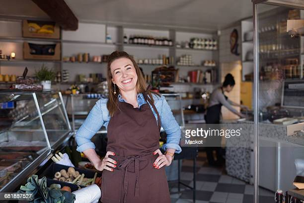 portrait of smiling woman standing with hands on hip at store - arms akimbo stock pictures, royalty-free photos & images
