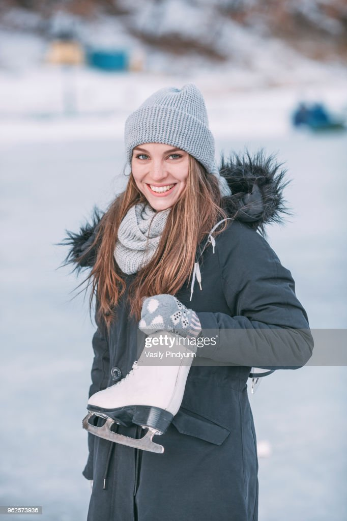 Portrait of smiling woman standing with ice skate : Stock Photo