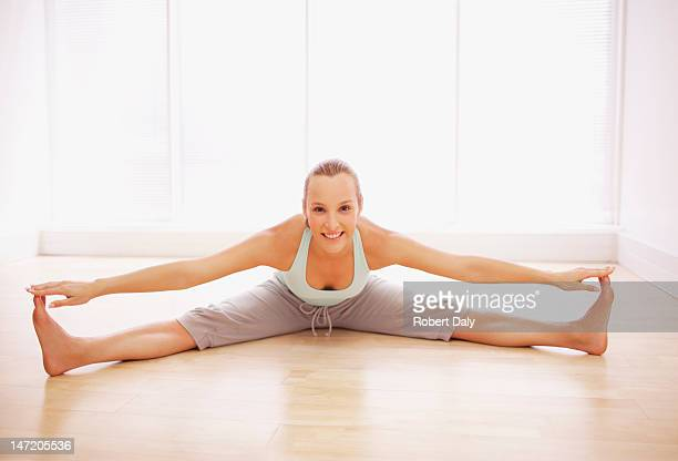 portrait of smiling woman stretching with legs apart - benen gespreid stockfoto's en -beelden