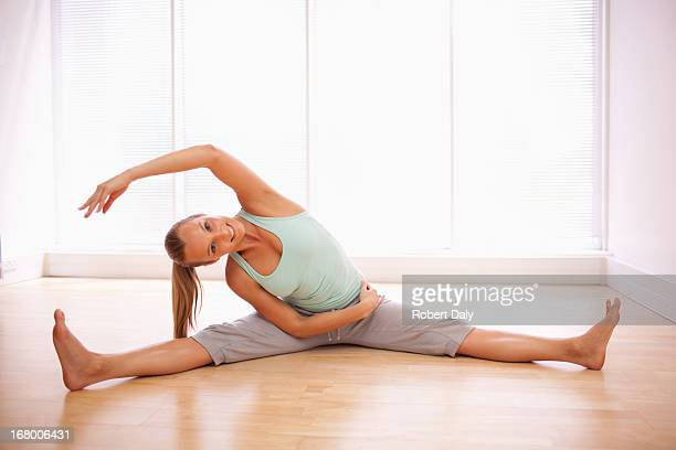 portrait of smiling woman stretching with legs apart - legs apart stock pictures, royalty-free photos & images