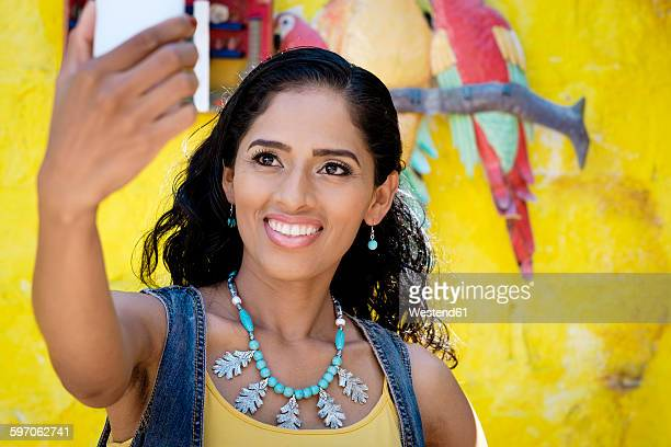 Portrait of smiling woman taking a selfie with smartphone