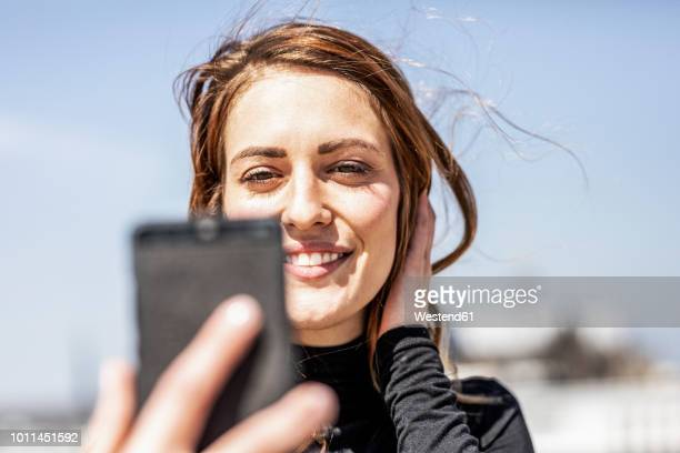 portrait of smiling woman taking selfie with smartphone - mid adult women stock pictures, royalty-free photos & images