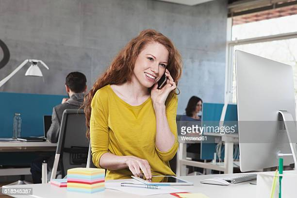 Portrait of smiling woman telephoning with smartphone at her workplace in the open space office