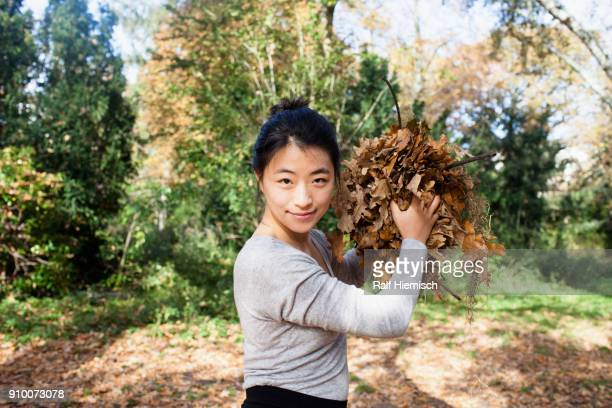 Portrait of smiling woman throwing dry leaves while standing at park