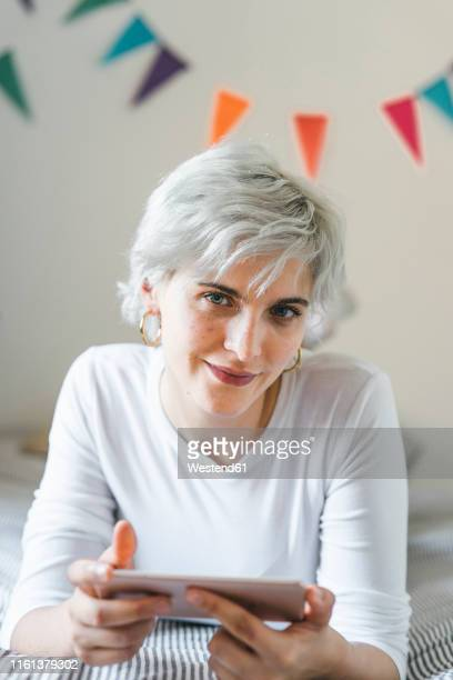 portrait of smiling woman using cell phone on bed at home - northern european stock pictures, royalty-free photos & images