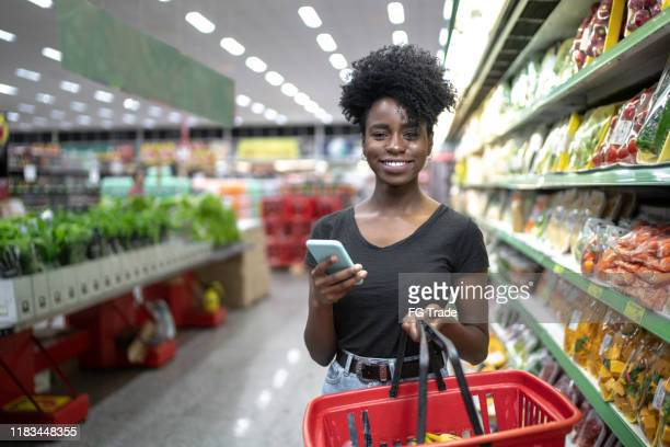portrait of smiling woman using phone and holding a shopping basket in supermarket - brazilian ethnicity stock pictures, royalty-free photos & images