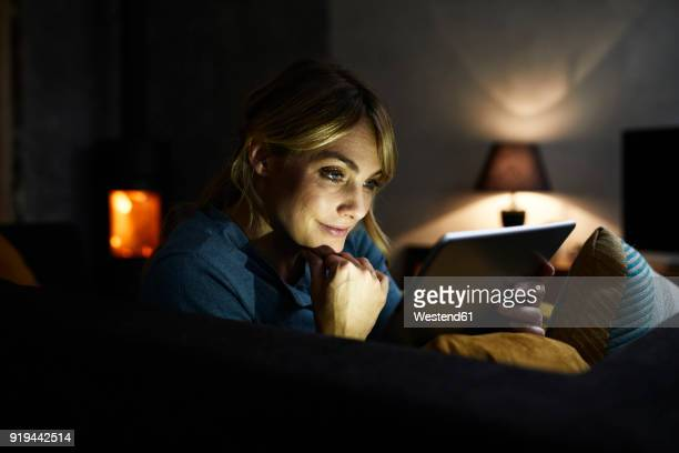 portrait of smiling woman using tablet on the couch at home in the evening - atmospheric mood stock pictures, royalty-free photos & images