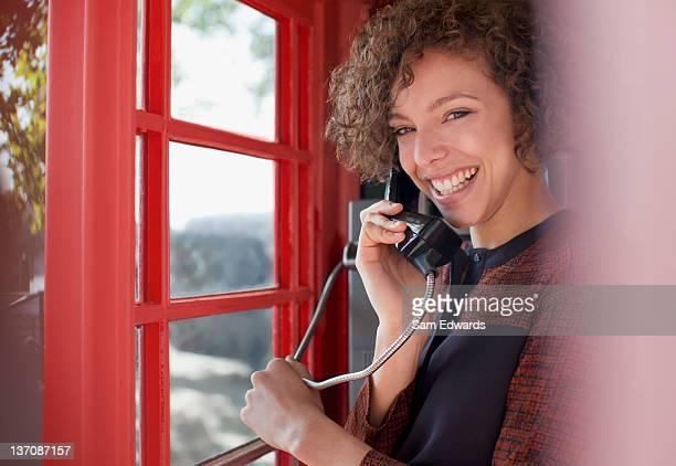 Portrait de femme souriante en cabine téléphonique