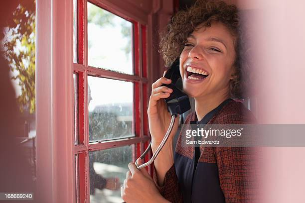 portrait of smiling woman using telephone booth - telephone booth stock pictures, royalty-free photos & images