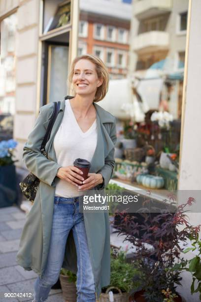 Portrait of smiling woman walking on pavement in front of a flower shop