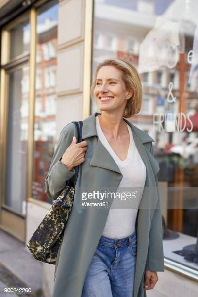 Portrait of smiling woman walking on pavement in front of a shop