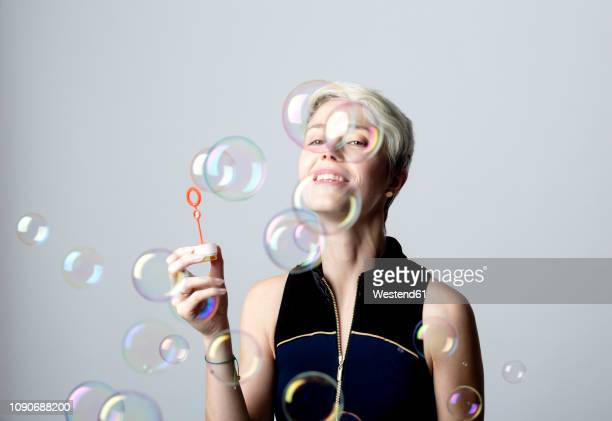 portrait of smiling woman watching soap bubbles - lightweight stock pictures, royalty-free photos & images