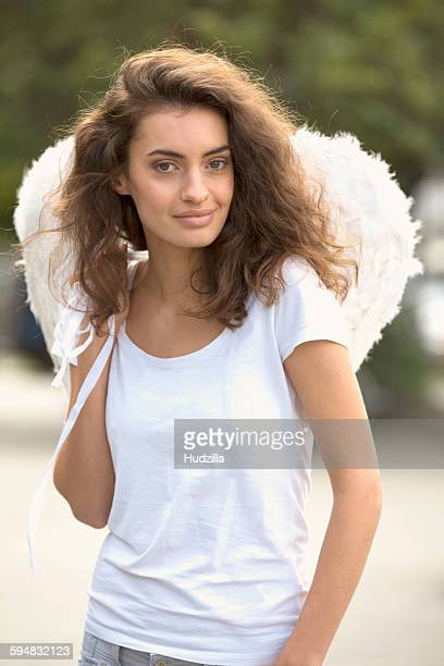 Portrait of smiling woman wearing angel wings outdoors