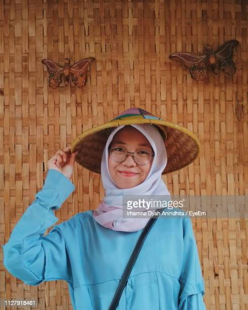 portrait of smiling woman wearing asian style conical hat - asian style conical hat stock pictures, royalty-free photos & images