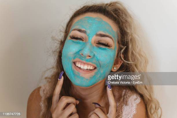 portrait of smiling woman wearing blue face mask at home - chelsea mask stock pictures, royalty-free photos & images