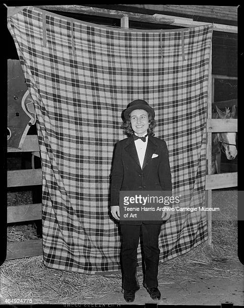 Portrait of smiling woman wearing dark suit necktie and hat posed in front of plaid blanket hanging from wood beams in front of horse stall in Hunt...