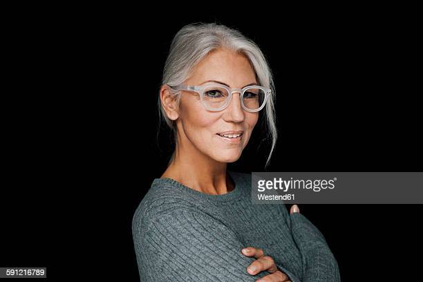 portrait of smiling woman wearing glasses in front of black background - black background stock pictures, royalty-free photos & images