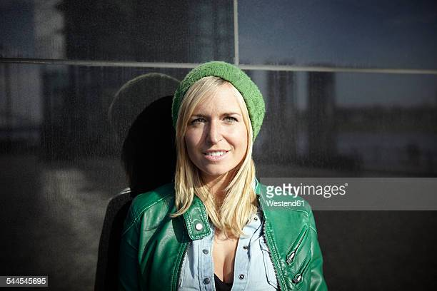 Portrait of smiling woman wearing green cap and leather jacket