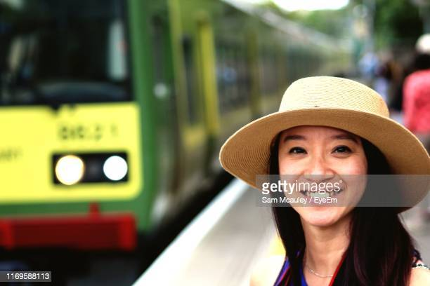 portrait of smiling woman wearing hat at railroad station - dalkey stock pictures, royalty-free photos & images