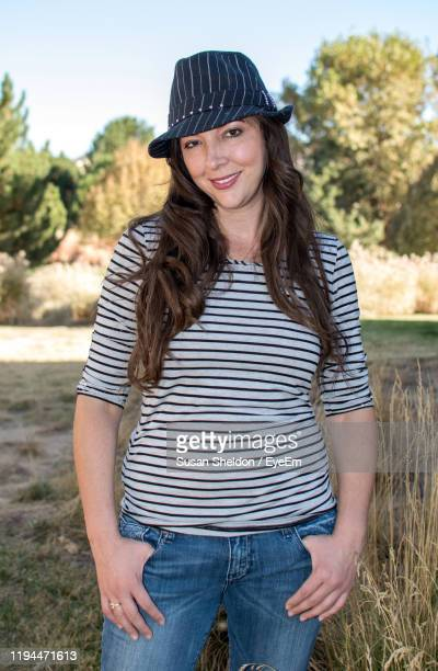 portrait of smiling woman wearing hat standing on land - by sheldon levis fotografías e imágenes de stock