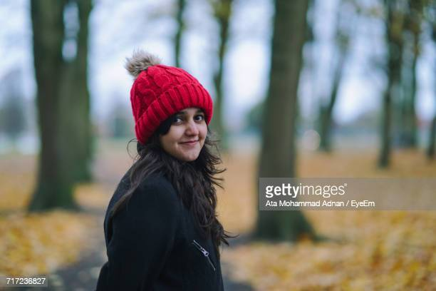 Portrait Of Smiling Woman Wearing Knit Hat Against Trees During Autumn