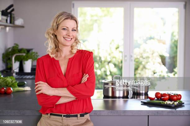 portrait of smiling woman wearing red blouse standing in kitchen - red shirt stock pictures, royalty-free photos & images