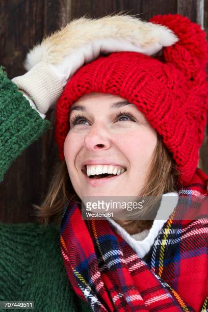 Portrait of smiling woman wearing red bobble hat and fur gloves in winter