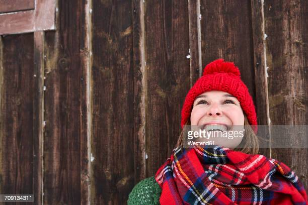 Portrait of smiling woman wearing red bobble hat in winter looking up