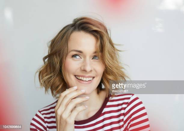 portrait of smiling woman wearing red-white striped t-shirt - women stock-fotos und bilder