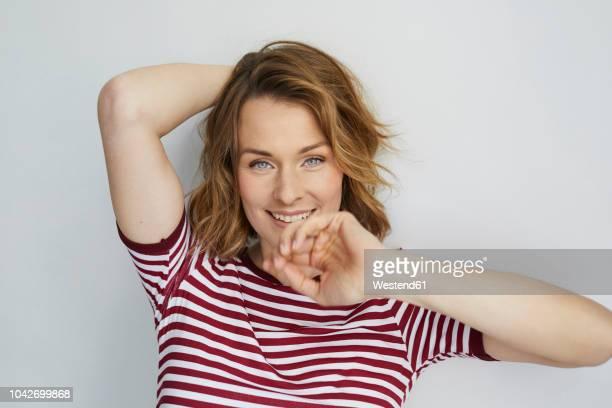 portrait of smiling woman wearing red-white striped t-shirt - hände hinter dem kopf stock-fotos und bilder
