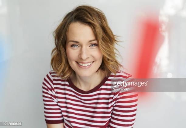 portrait of smiling woman wearing red-white striped t-shirt - 35 39 jahre stock-fotos und bilder
