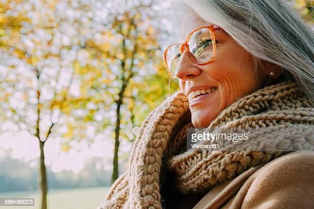 Portrait of smiling woman wearing scarf and glasses